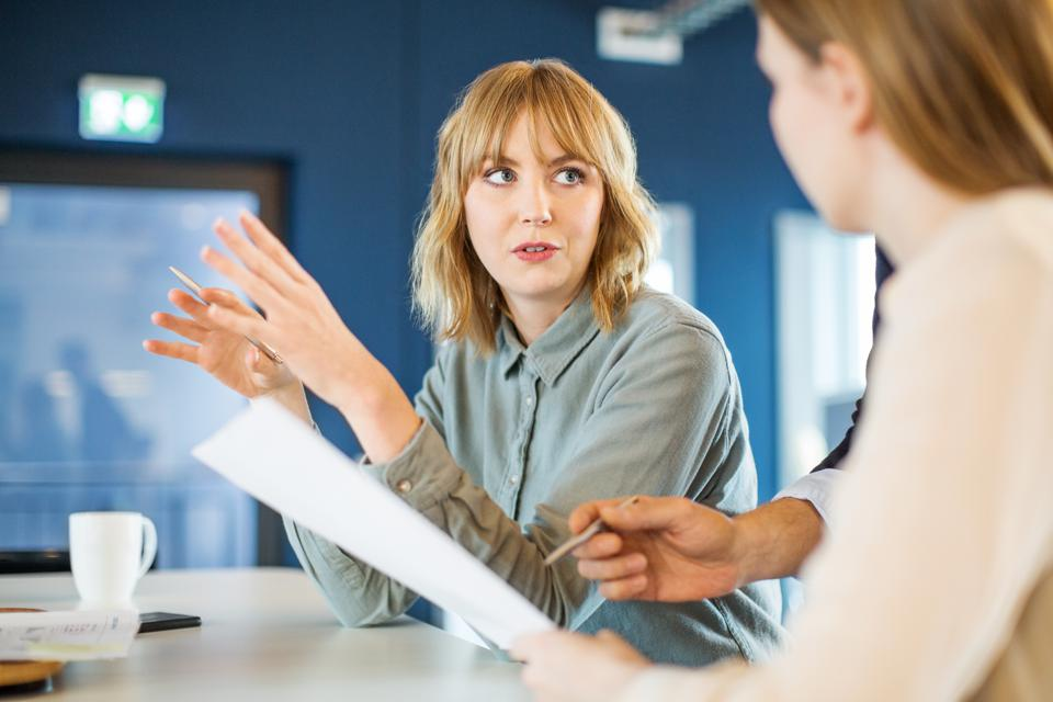 Businesswoman sharing ideas with colleague in meeting