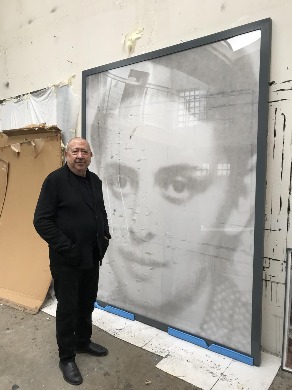Christian Boltanski standing by a large printed photograph of a woman, in his studio.