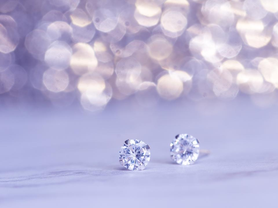 A set of diamond earrings on a purple background.