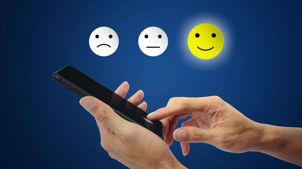 An illustration of a person using a smartphone to rate their experience by choosing a smiling emoji.