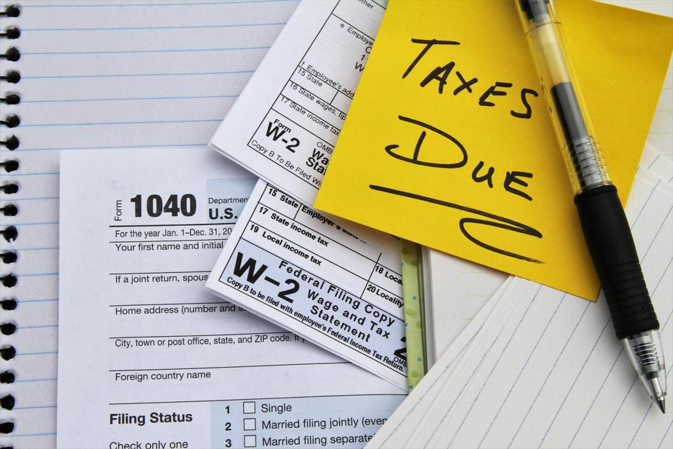 Tax return forms and wage statements with note Taxes Due.