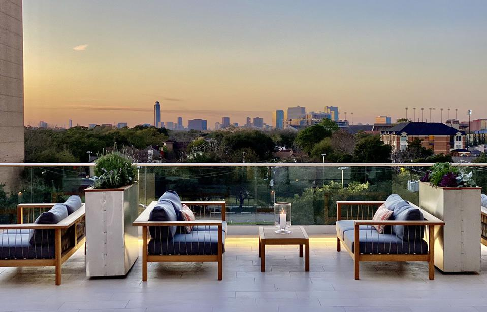 Terrace seating on the fifth floor has views of treetops in a neighborhood near Rice University.