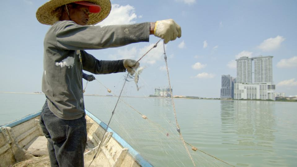 Portuguese fisherman with new development areas and Melaka Gateway in the background.