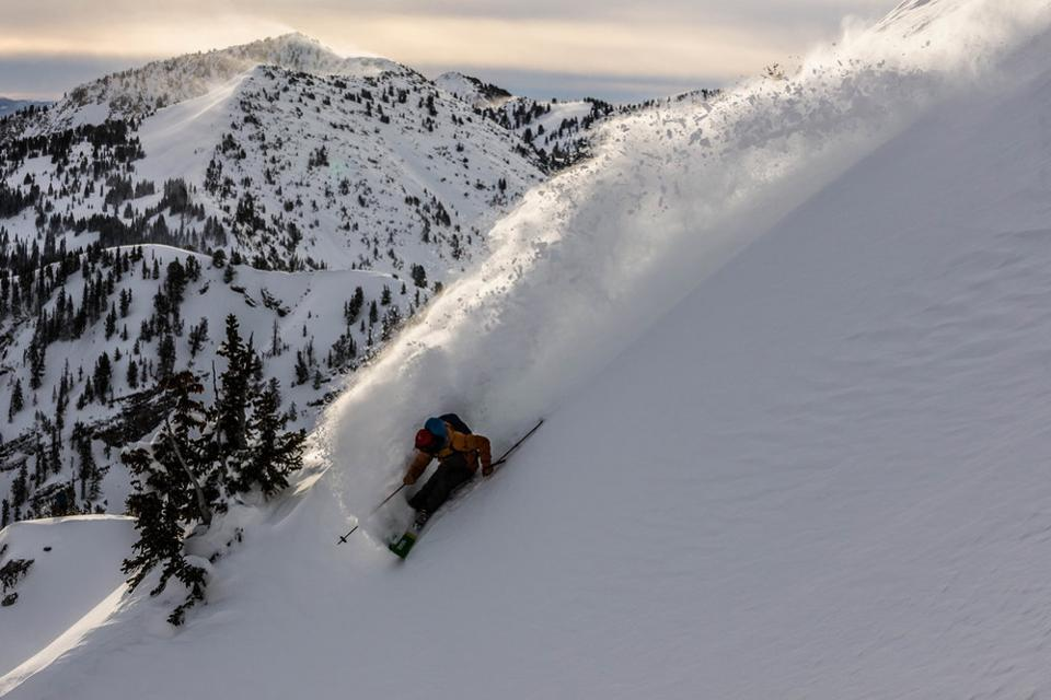 A skier going down the slopes.