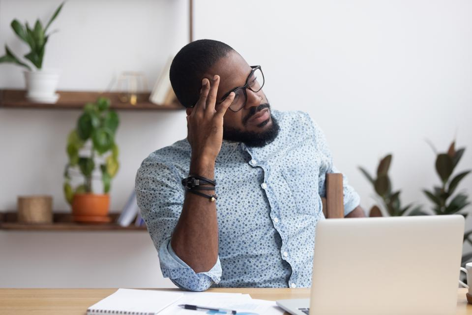 Serious thoughtful african businessman sitting at desk