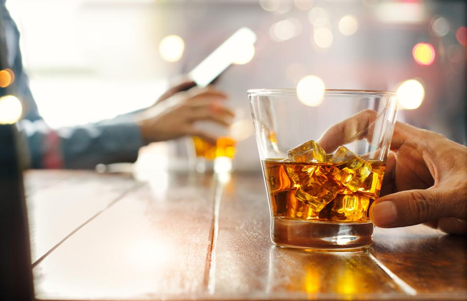 Close-up of two men clinking whiskey drink alcoholic beverage at bar counter in the pub background.