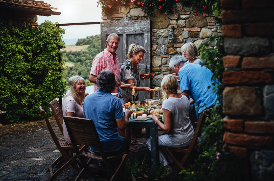 A family dines outside at a house swapped through Home Exchange