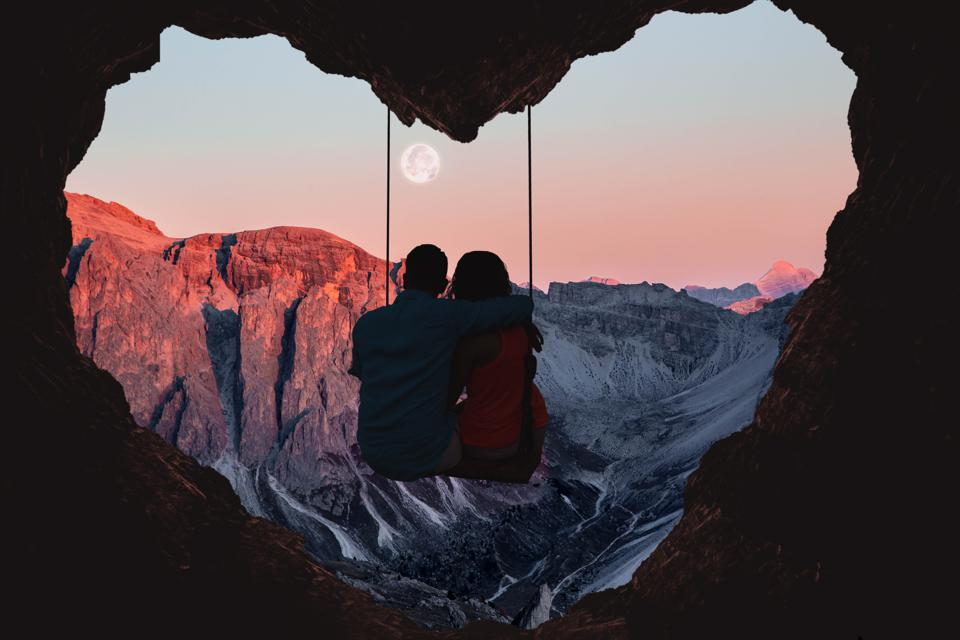 Couple on swing contemplating the mountains in a romantic view with heart shape.