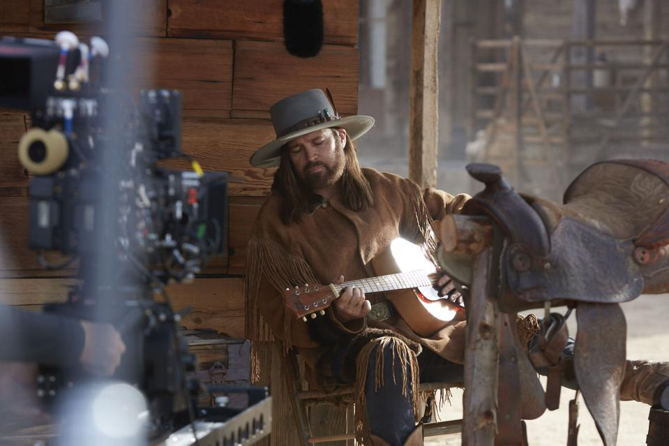 Billy Ray Cyrus plays his guitar on the set of a Super Bowl commercial for Doritos.