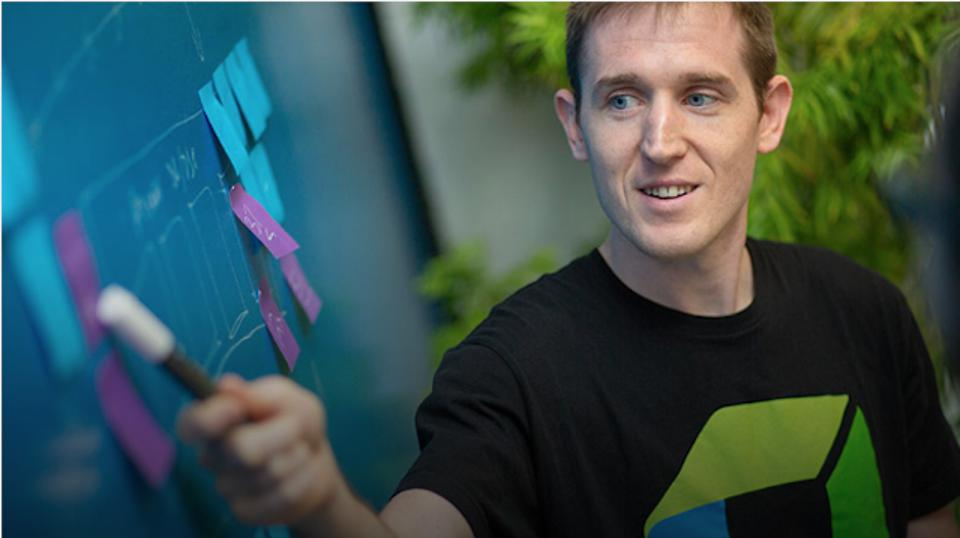 A man pointing at a 'Kanban' flow chart and Post-It notes with a marker pen.