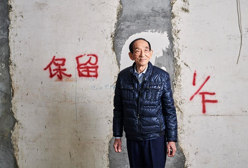 Tang in a building he owns in Mong Kok district. The red letters on the wall read ″keep″, indicating load-bearing walls that can't be knocked down for renovation.