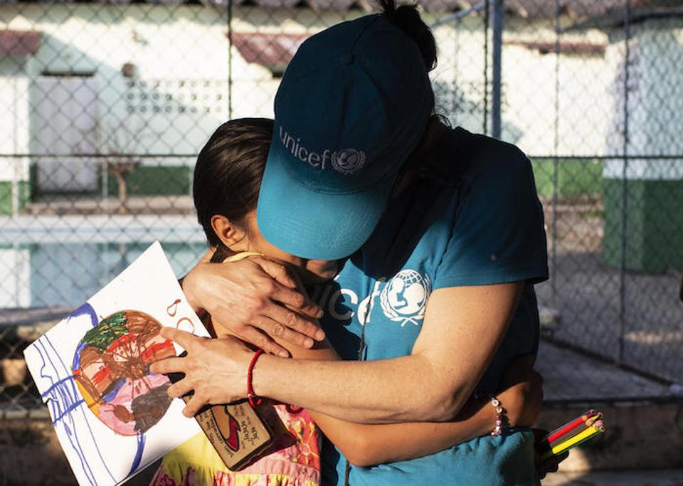 In Mexico, a UNICEF volunteer hugs a 10-year-old girl whose mother was murdered by gang members in San Pedro Sula, Honduras. She and her older siblings traveled north, hoping to find safety in the United States.