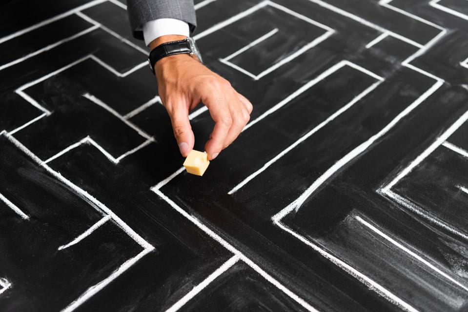 Businessman moving cheese in maze