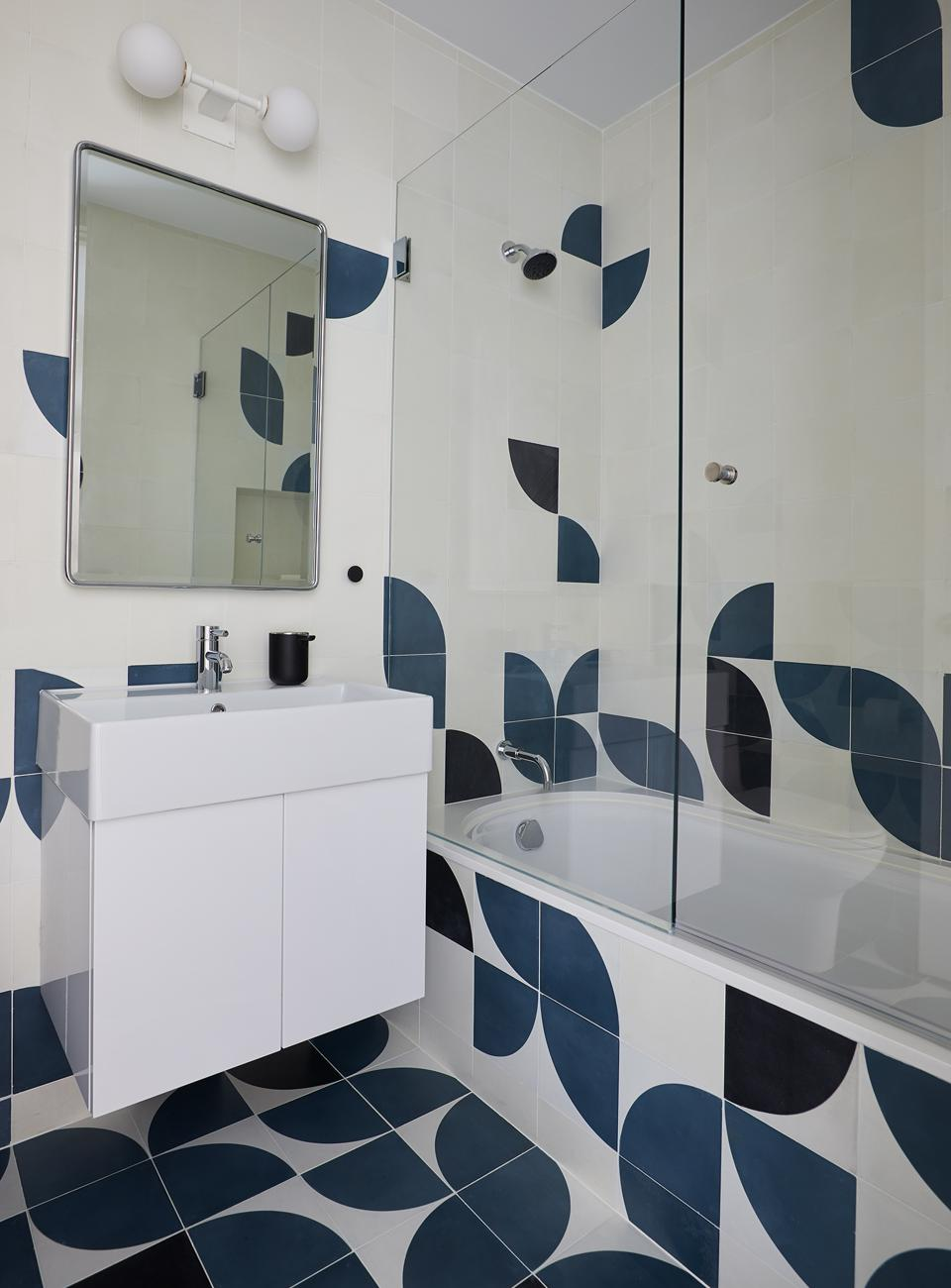 The guest bathroom features tiles from Clé Tile, and Bastion Light from Allied Maker.