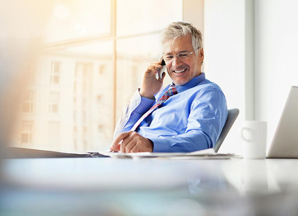 Businessman sitting at desk, talking on the phone