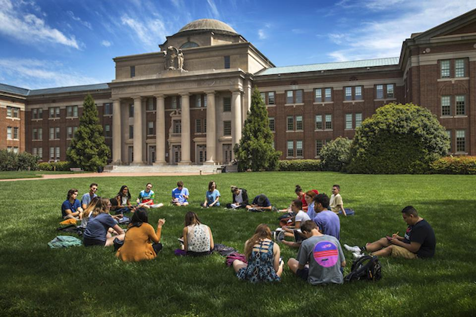 Davidson College students sit on the lawn for an outdoor class on a sunny day