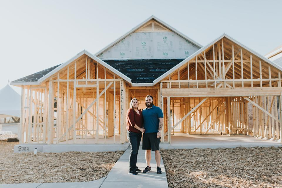 Air Force veterans Kyle and Reese Hines in front of their home under construction in San Antonio.