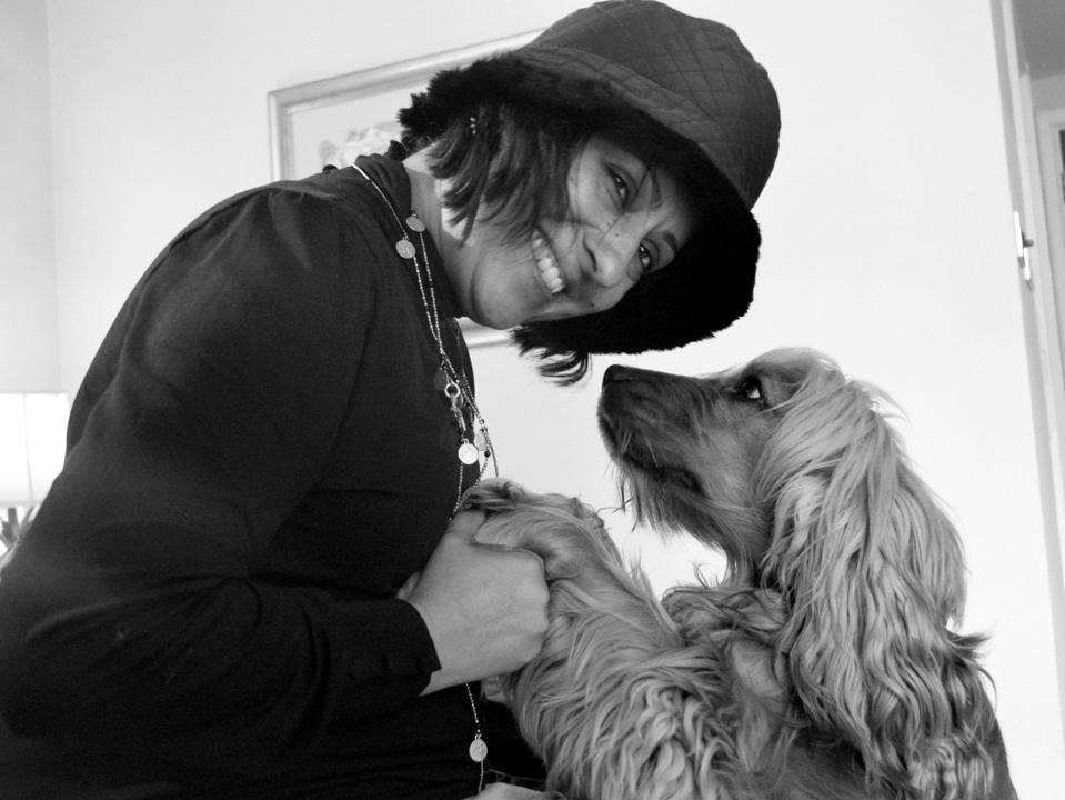 Black and white photo of Jyoti wearing a hat and greeting her dog.