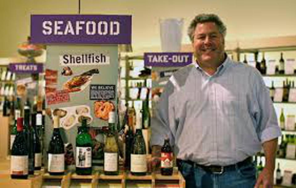 Image of owner Tom Genoise standing by a colorful seafood display at Bottlerocket wine shop
