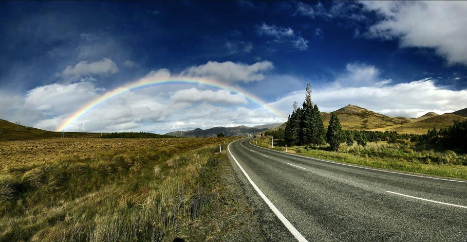Country road leading to clouds and a rainbow.