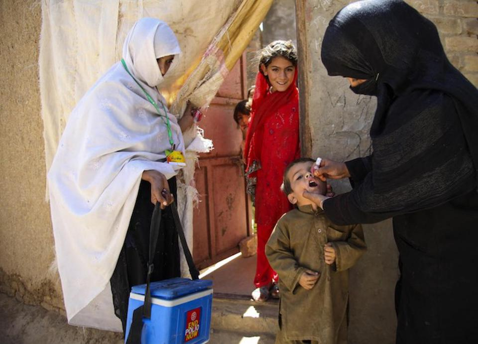 A UNICEF-trained health worker, right, vaccinates a child against polio outside the family home in Quetta, Balochistan Province, Pakistan.