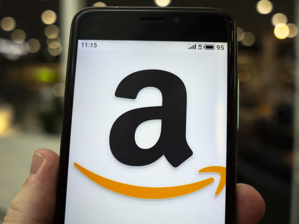 In this photo illustration the Amazon logo is seen displayed...