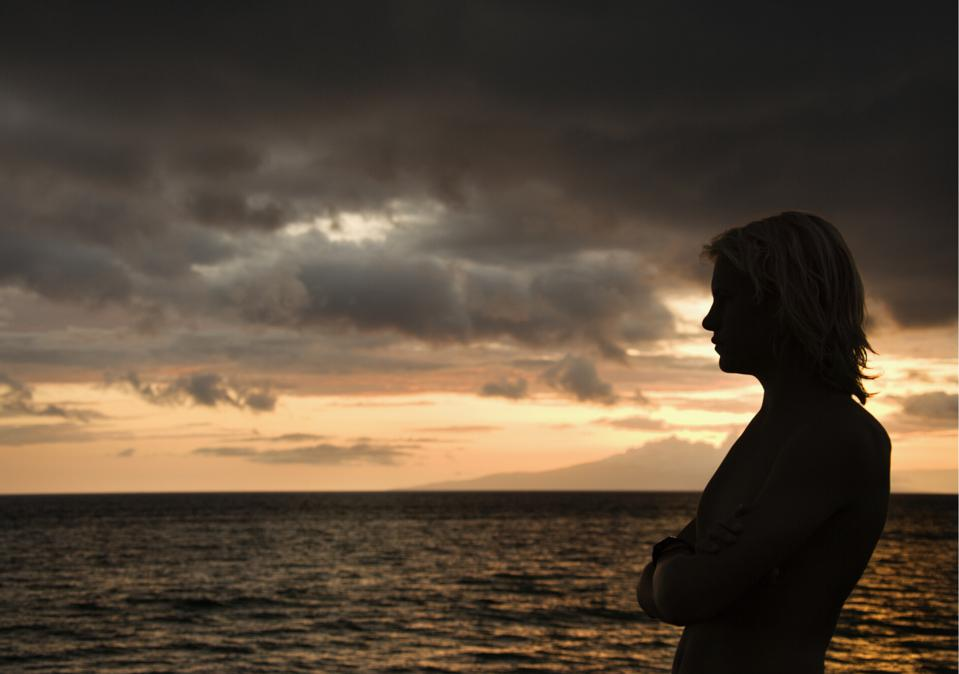 A woman looks at the ocean while the sun is setting in a cloudy sky behind her.
