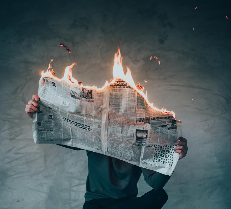 Man holding a newspaper that is on fire.