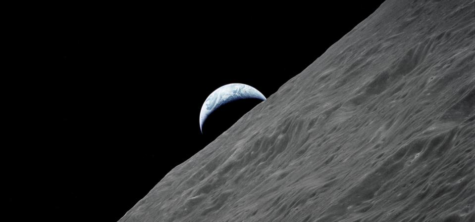 The crescent Earth rises above the lunar horizon in this spectacular photograph taken from the Apollo 17 spacecraft in lunar orbit during final lunar landing mission in the Apollo program.
