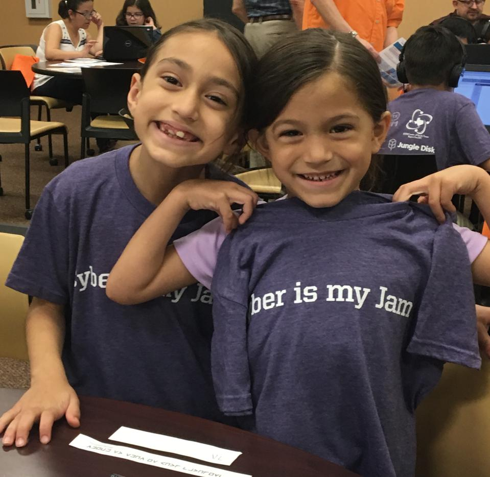Two girls proudly display their ″Cyber is My Jam″ t-shirts.
