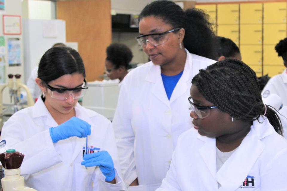 M. Nia Madison and students working in a science lab.