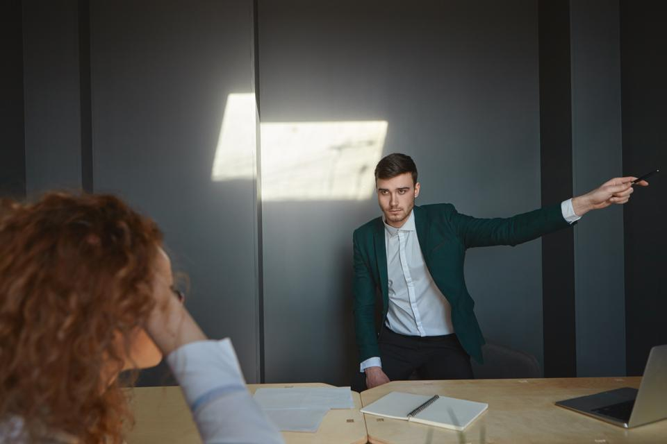 Furious male boss scolding young woman intern for poor discipline, dismissing her, pointing finger at the door. Stressed female employee sitting at desk, listening to irritated employer yelling at her