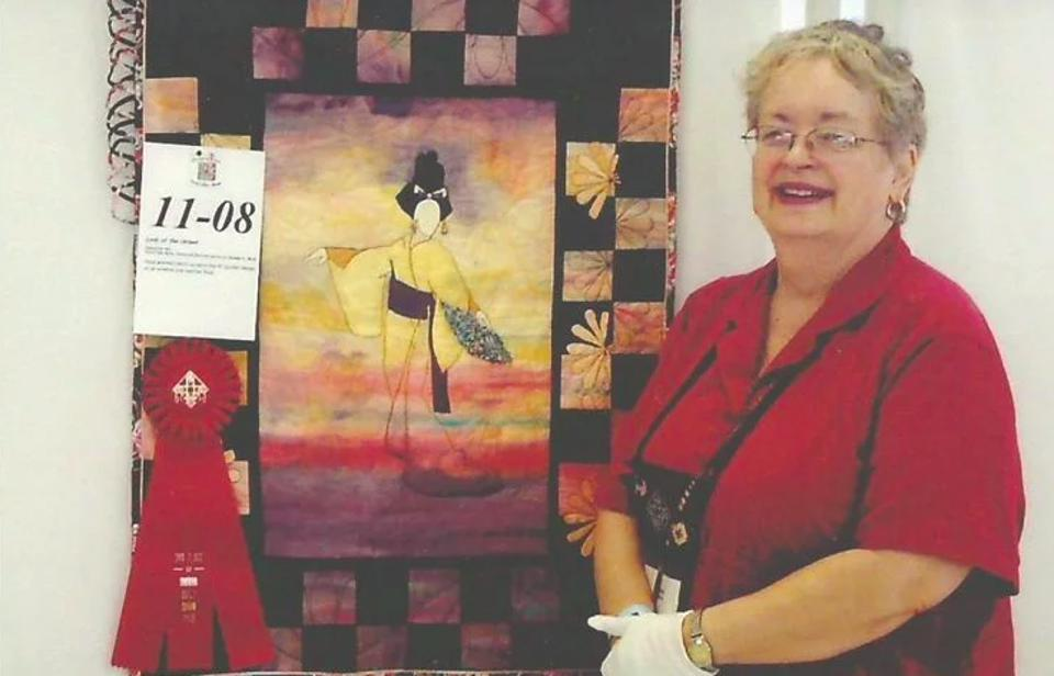 Photo of talented quilter and artist DeAnne Mack with her work