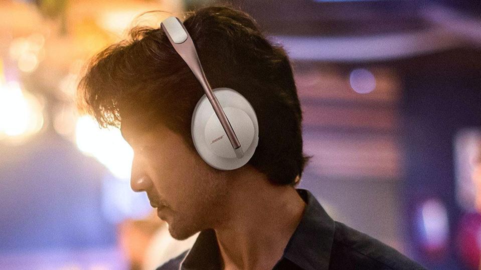 Person wearing white Bose Headphones 700.