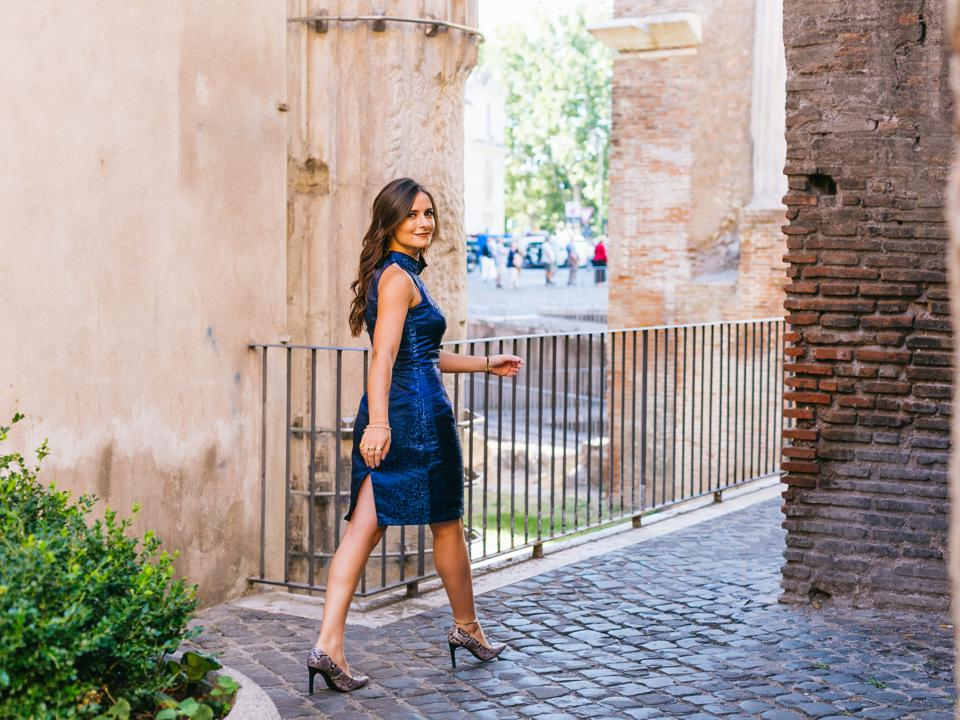 attractive woman in blue dress and heels walking through the streets of rome italy