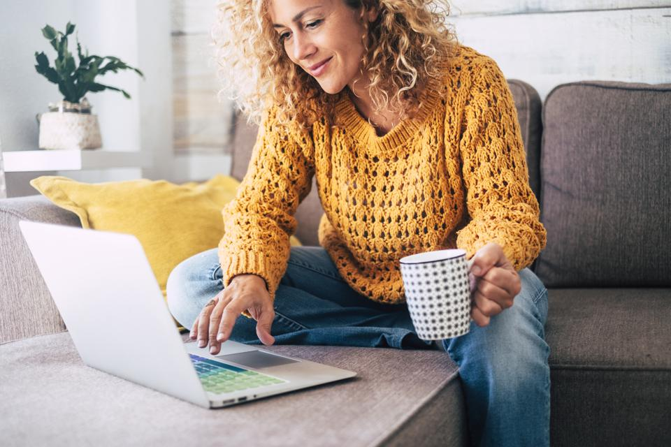 Nice beautiful lady with blonde curly hair work at the notebook sit down on the sofa at home - check on oline shops for cyber monday sales - technology woman concept for alternative office freelance