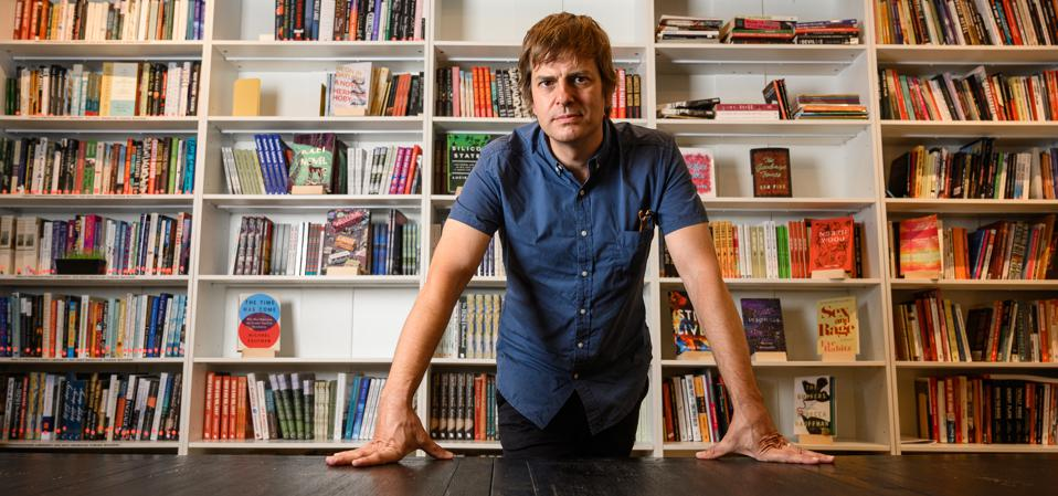 A picture of Andy Hunter, founder of Bookshop.org, standing in front of a row of bookshelves.