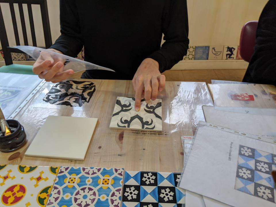 A visitor uses a stencil to create a new Azulejo tile at the Os Azulejos do Porto workshop in Porto.