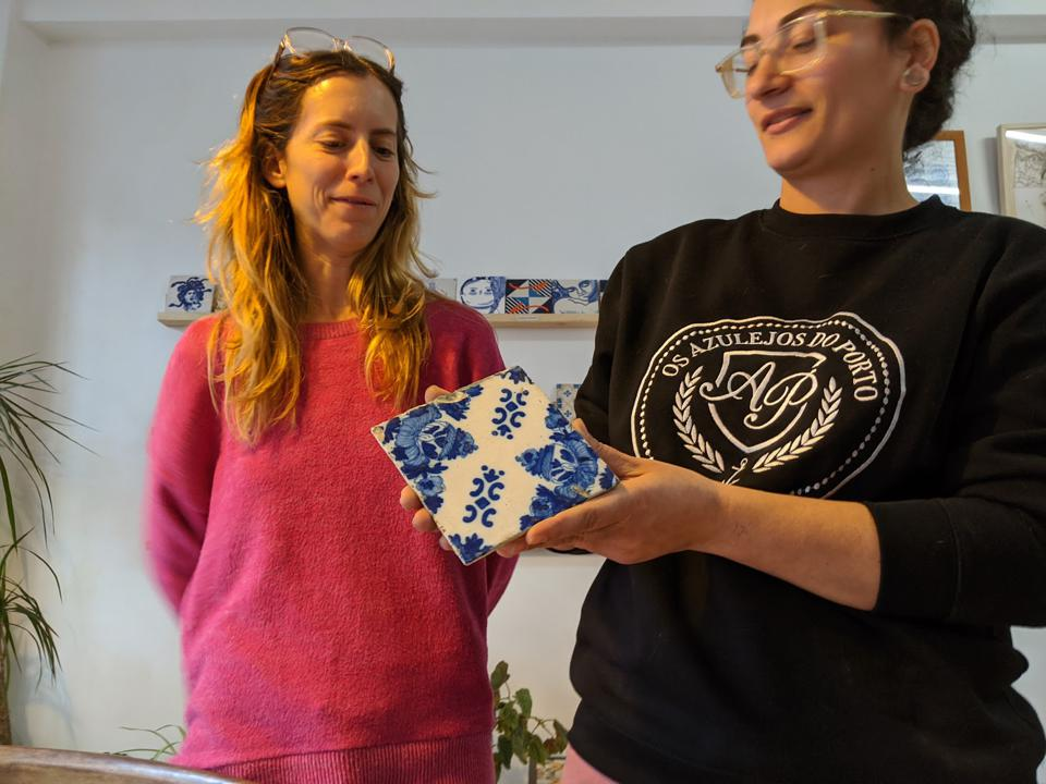 Alba Plaza and Marisa Ferreira show one of the Azulejo tiles from their collection. The women are trying to catalog and preserve as many tiles as possible before the ceramic art is lost to renovations.