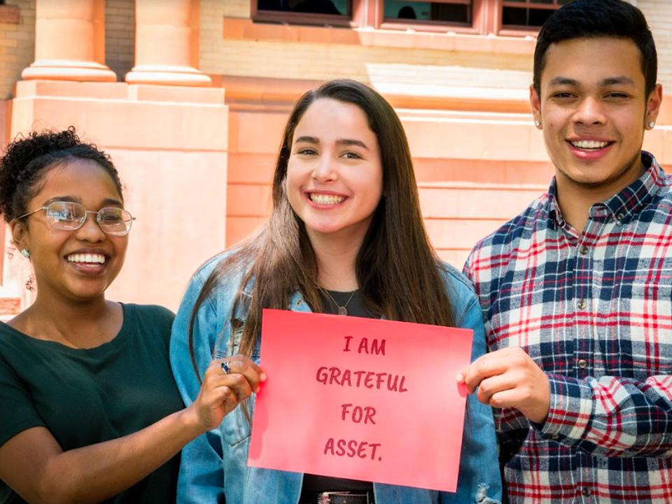 Three diverse students who benefited from ASSET Education pose with a thank you sign.