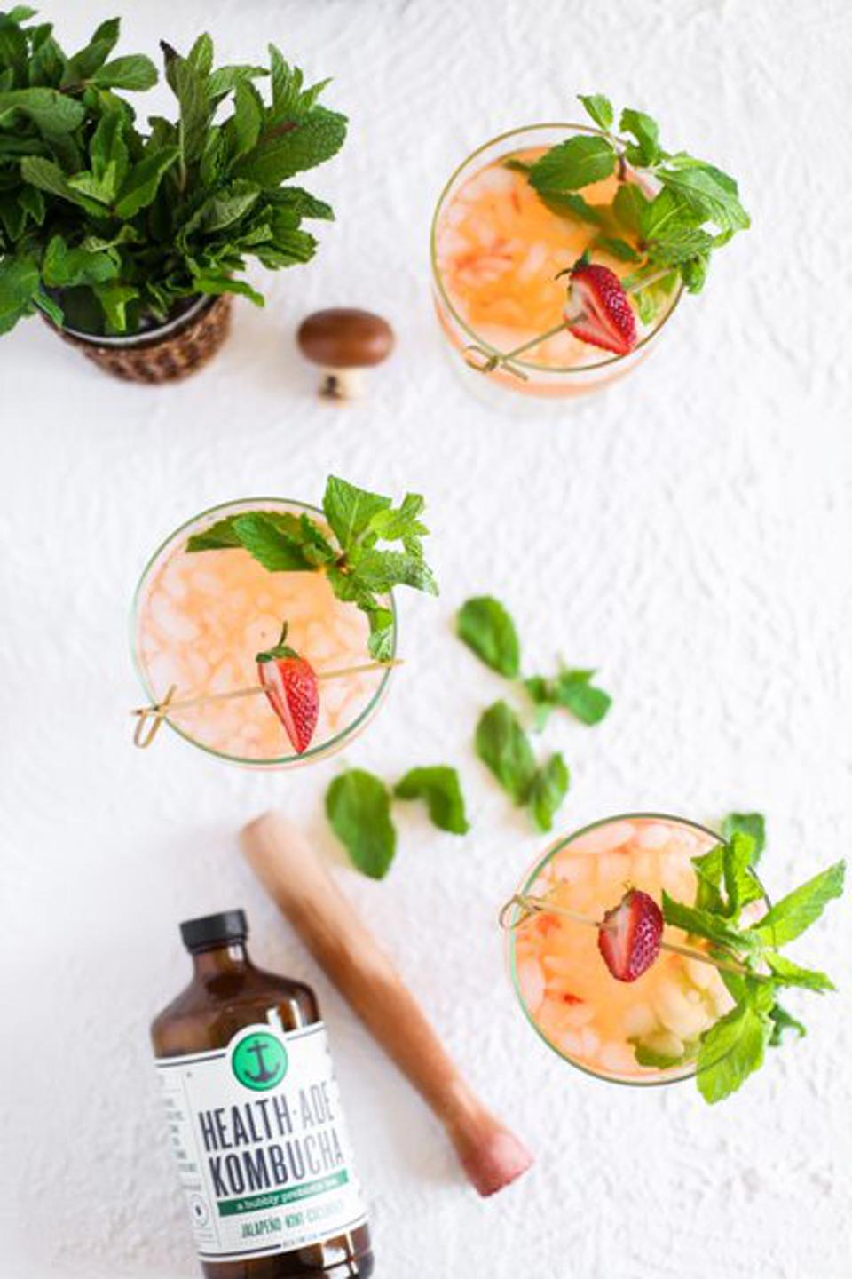 Aerial photo of cocktails garnished with strawberries. Muddler also pictured.