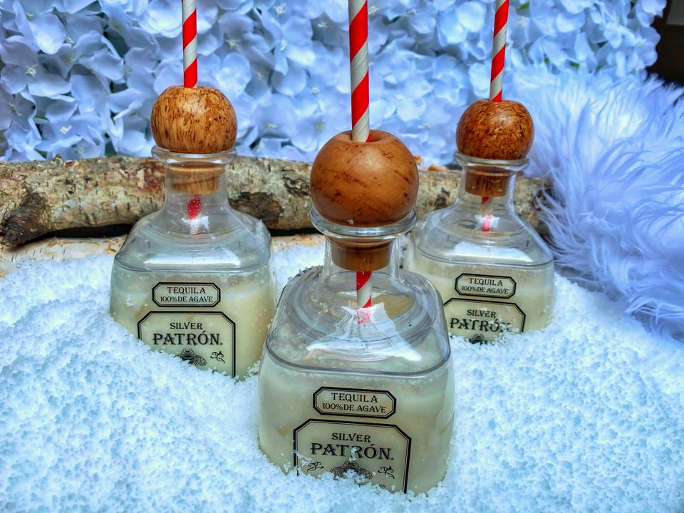 Mini PATRÓN bottles with margaritas in them; straw through the top of each bottle.