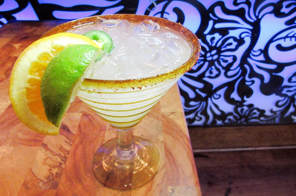 Margarita garnished with orange and lime slice, and salted rim.