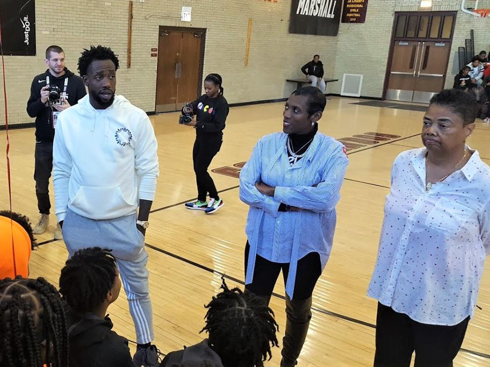 Pat Beverley talks to the boys and girls teams at Marshall High while his mother, Lisa Beverley (middle), looks on. Legendary Marshall girls' coach Dorothy Gaters (right) looks on. Beverley is a point guard for the Los Angeles Clippers, in town for the NBA's All-Star weekend.