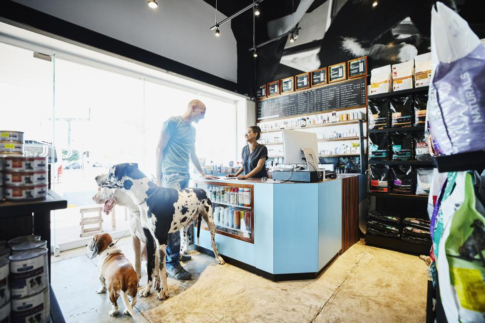 Smiling pet store owner helping customer with dogs check out
