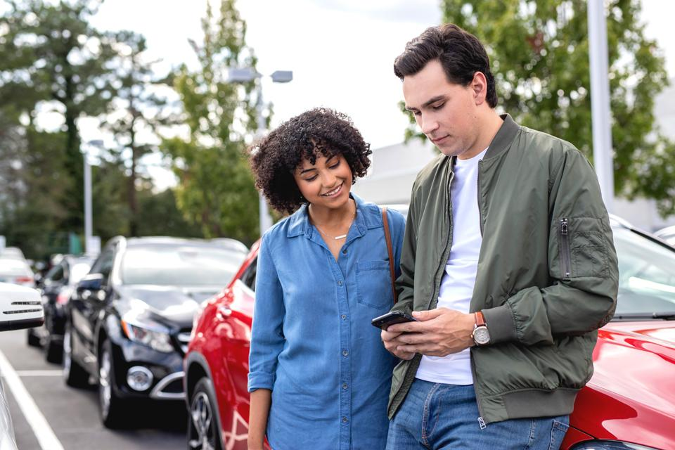 two people looking at phone on car