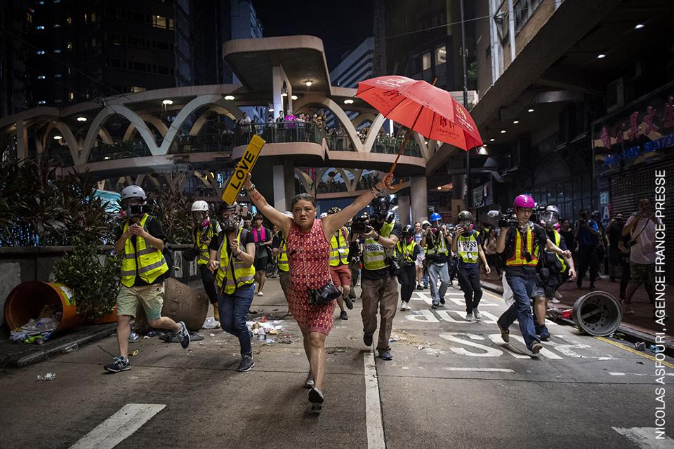 A woman holds up an umbrella (a symbol of protest)