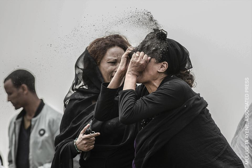 A relative of a victim of Ethiopian Airlines flight crash throws dirt in her face