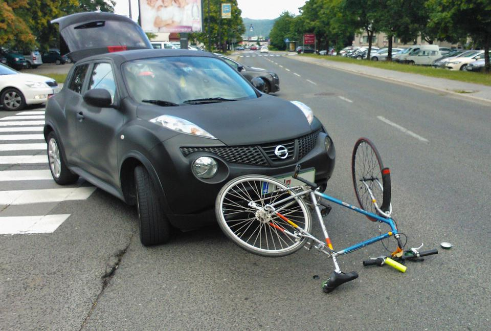 Bicycle on the ground after being hit by a car
