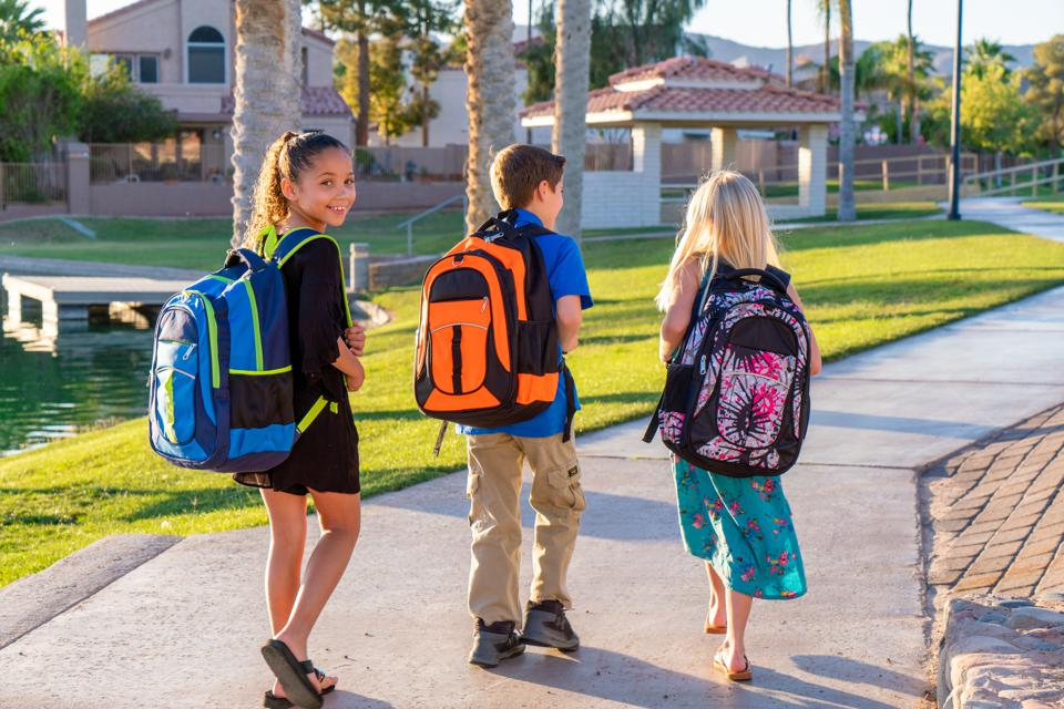 Three grade school children wearing colorful backpacks walk together along a path on a sunny morning.